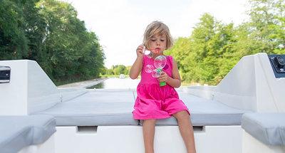 Bimba che gioca sul ponte della barca
