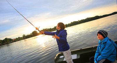 Bambino che pesca dalla barca