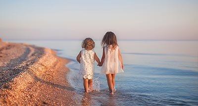 Due bambini che camminano sulla spiaggia