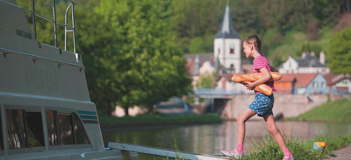 Bambina che porta il pane a bordo di una barca Le Boat