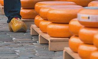 Forme di Gouda impilate inun mercato di formaggi